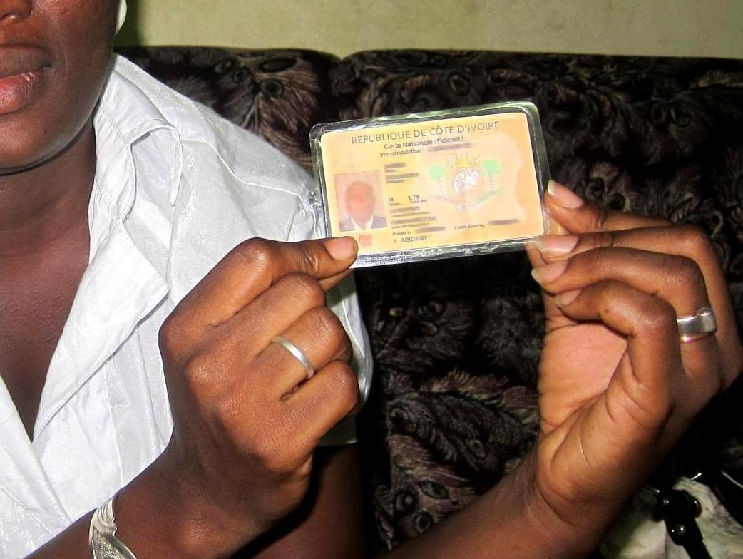 A Woman Displays The Id Card Of Her Missing Father