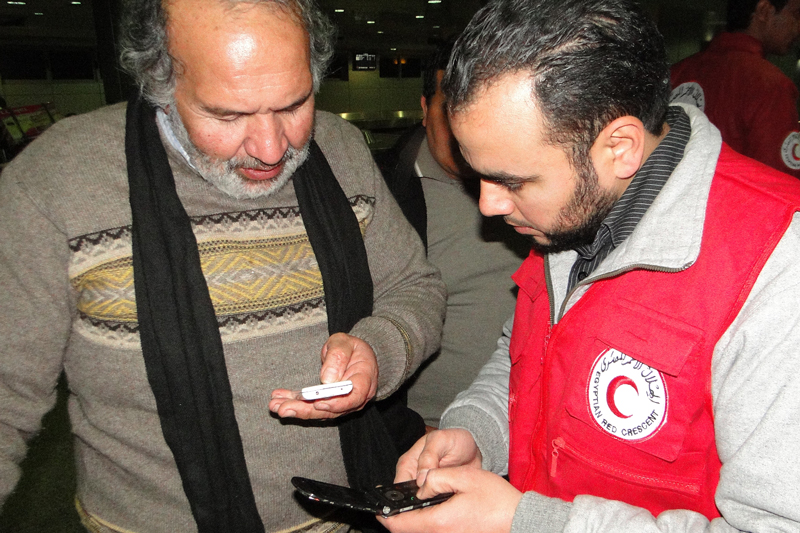 An Egyptian Red Crescent volunteer helps a man who has just returned from Libya to call his family in 2015.