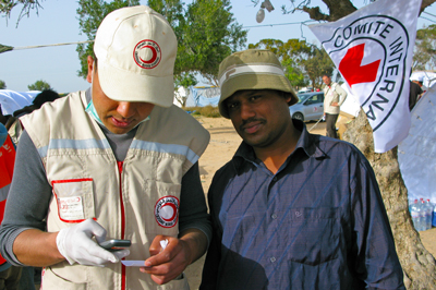 A man from Bangladesh who has fled the conflict in Libya calls his family from Choucha Camp, near the Libyan border, with the help of a Tunisian Red Crescent volunteer.
