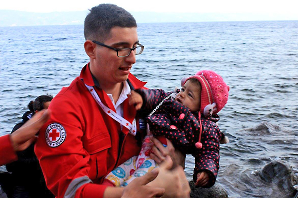 A Hellenic Red Cross volunteer carries a child who has just arrived on one of the Greek islands from Turkey.