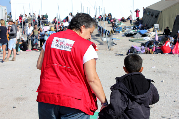 Oxy Transit Point, Molyvos, Lesvos, Greece. A Hellenic Red Cross worker specialized in restoring family links looks after a young migrant.